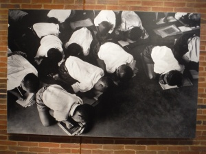 Children trying to do their lessons on the floor in a crowded school.